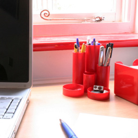 Image of red desk organizing tools and a laptop.