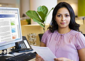 Woman at computer holding stack of papers