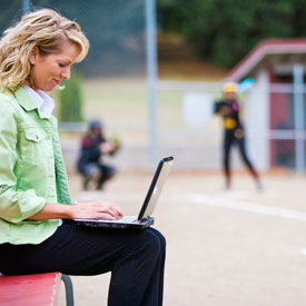 Mother working on laptop while at a child's baseball game