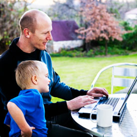 Father working on laptop outdoors with young son