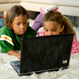 Two children lying on floor looking at HP notebook PC.