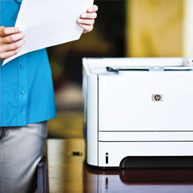 Woman holding document next to LaserJet