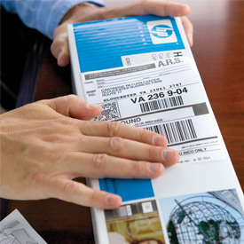 Hands placing return label on toner box