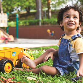 boy in a park with a yellow toy dump truck