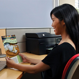 Woman looking at marketing piece from HP Officejet Pro 8500A