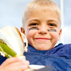 smiling boy with trophy