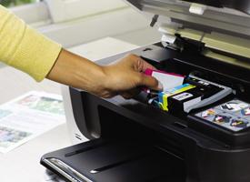 woman replacing ink cartridge in inkjet printer